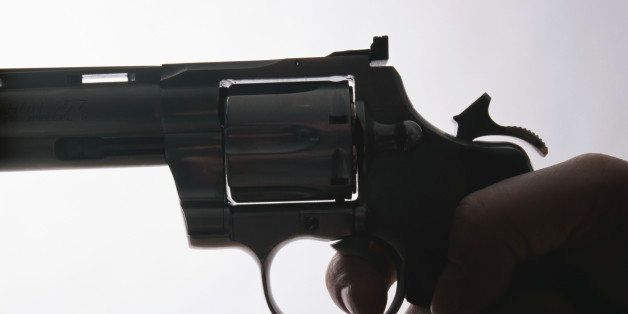 Hand holding gun, close-up, side view