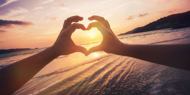 Couple formed heart shape with their hands against sunset over the horizon.