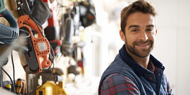 Portrait of a handsome young handyman standing in front of his work tools