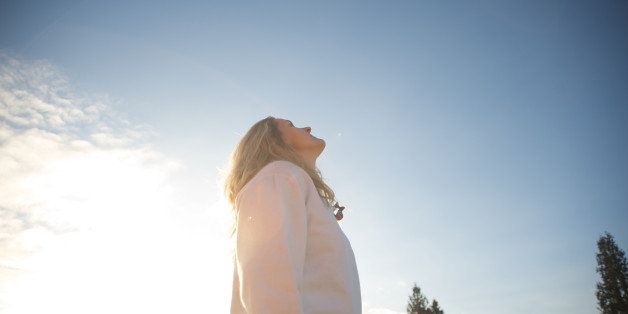 A woman looks into the sky on a sunny day.