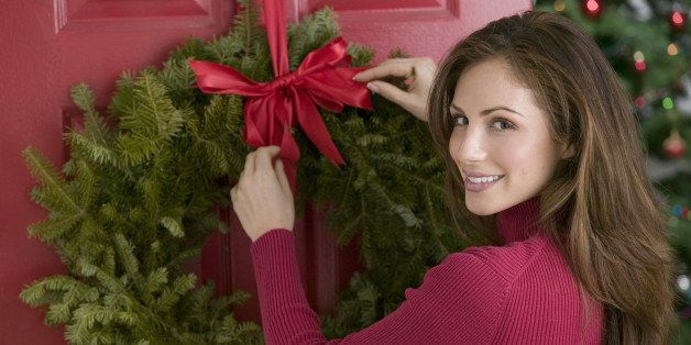 woman hanging wreath - When Did We Start Celebrating Christmas