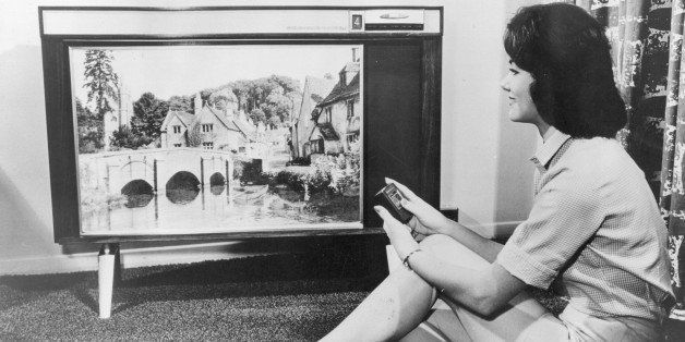 A woman watching a large RCA television.