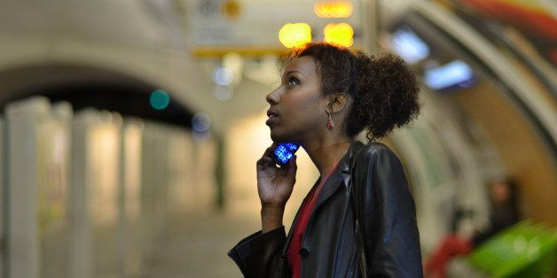 Young woman using mobile phone in a metro station