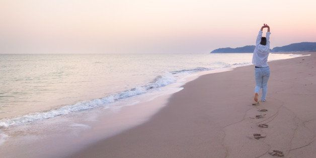 Landscape image of a Japanese woman stretches out her hands while walking on a beach in dawn. This image was taken in April 2