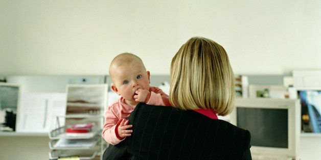 Woman working at desk holding baby girl (9-12 months), rear view