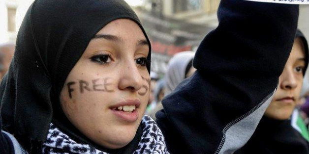 "A young woman with the words ""Free Syria"" written on her face attends a demonstration against violence in Syria on"