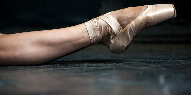 Close-up classic ballerina's leg in pointes on the black wooden floor