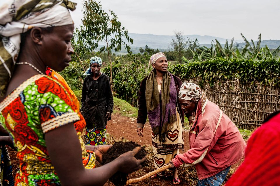 Adeline Nsimire (third from left), director of SAMWAKI, works with a group of sexual violence survivors as they plant crops i