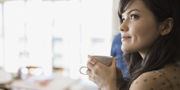 Smiling woman with coffee looking away