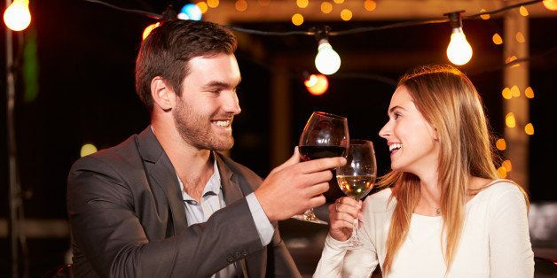 Couple eating dinner at rooftop restuarant holding glasses of wine