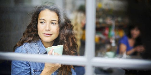 Lifestyle image of woman looking out of a cafe window whilst holding a drink.
