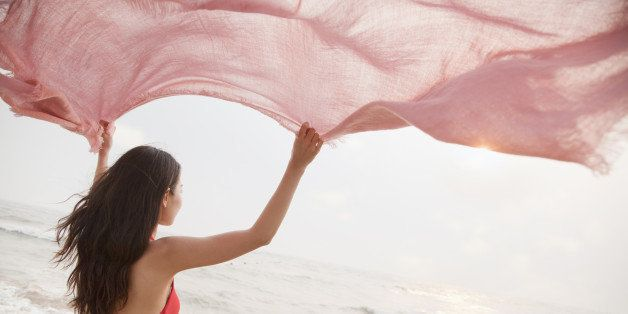 Young women on the beach holding scarf in the air and looking into the distance
