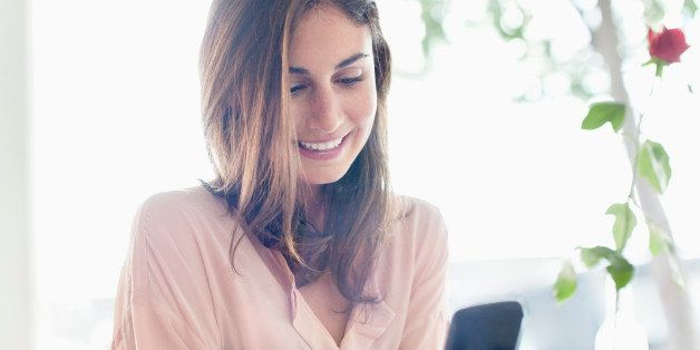 Smiling businesswoman checking cell phone