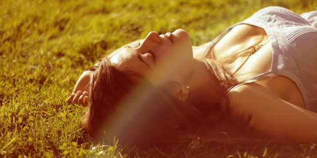 Girl enjoys sun, there's a warm summer mood around she is lying on grass.