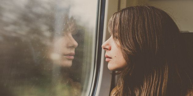 Woman looking through a window in a train with reflection.