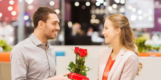 love, romance, valentines day, couple and people concept - happy young man with red flowers giving present to smiling woman a