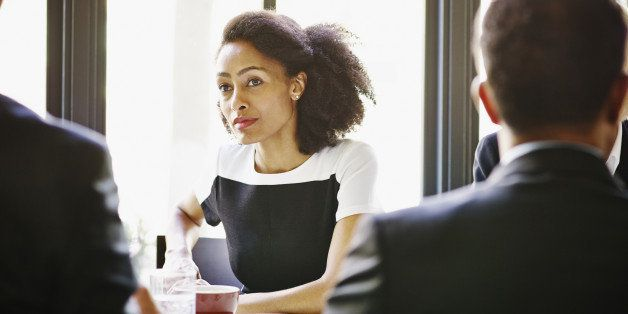 Businesswoman sitting at table in restaurant listening to colleagues in meeting
