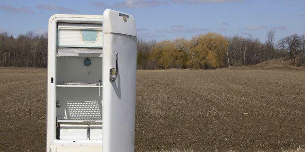 Old open fridge on roadside by farmers field.