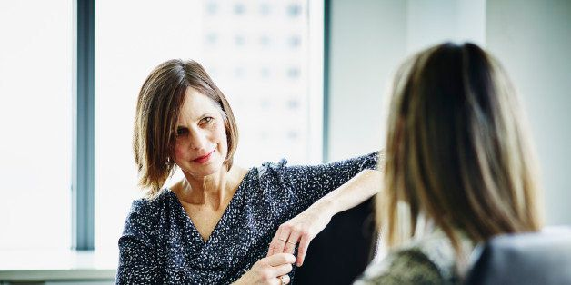 Mature businesswoman in discussion with female colleague at conference table in office