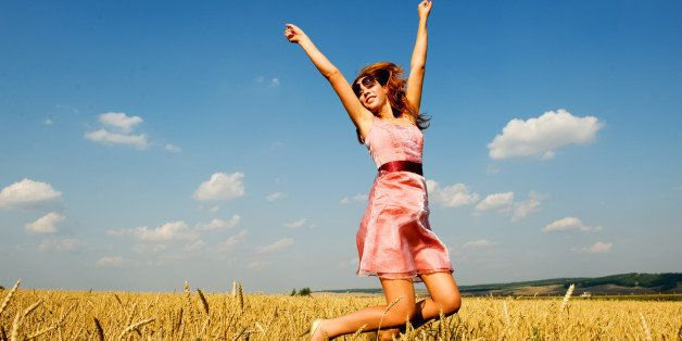 Happy woman jumping in golden field