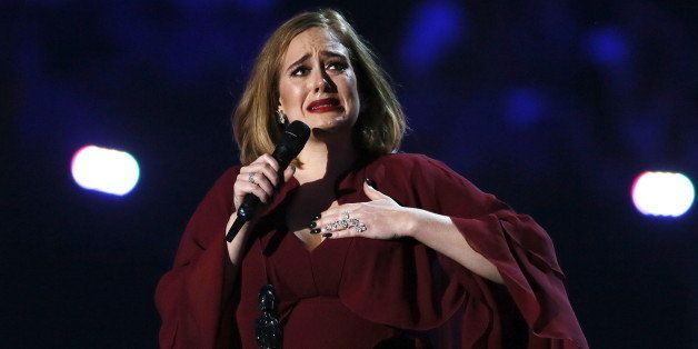 Adele reacts as she accepts the global success award at the BRIT Awards at the O2 arena in London, February 24, 2016. REUTERS