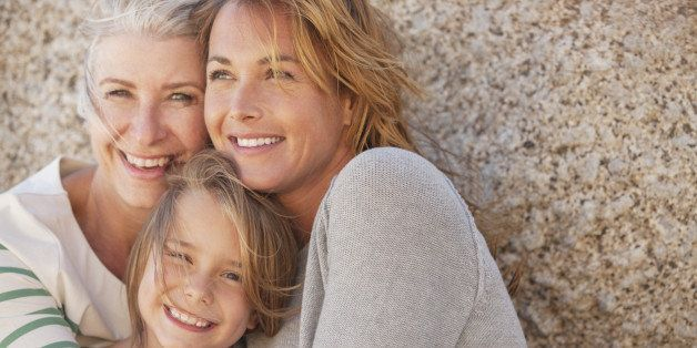 Three generations of women smiling outdoors