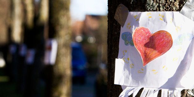 note with red heart sticking on tree
