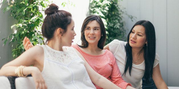 women talking together on sofa outdoor