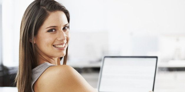 Portrait of an attractive young woman sitting at a desk with a laptop in front of her