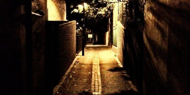 An empty and intimidating back street in North London illuminated by a single street lamp.