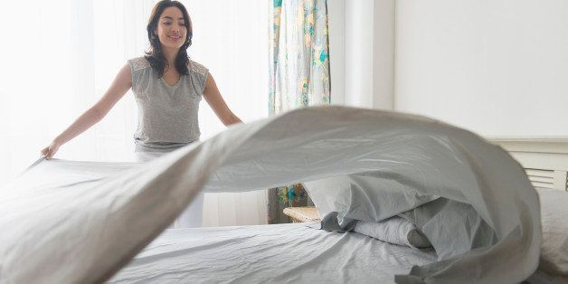 USA, New Jersey, Young woman spreading sheet on bed