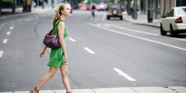 Woman walking in crosswalk in city