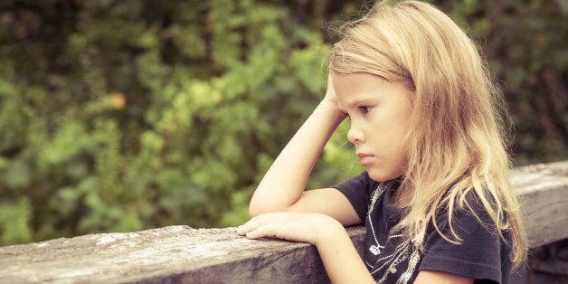 Portrait of sad blond little girl sitting on the bridge at the day timePortrait of sad blond teen girl sitting on the bridge