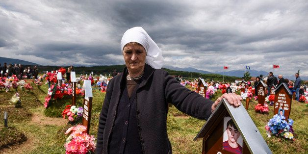 TOPSHOT - A Kosovo Albanian woman stands by the grave of her son during a ceremony to mark the Day of Missing Persons at the