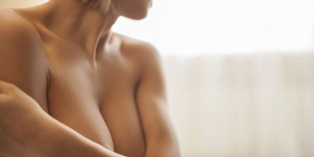 Cropped image of beautiful young shirtless woman covering breast with hands