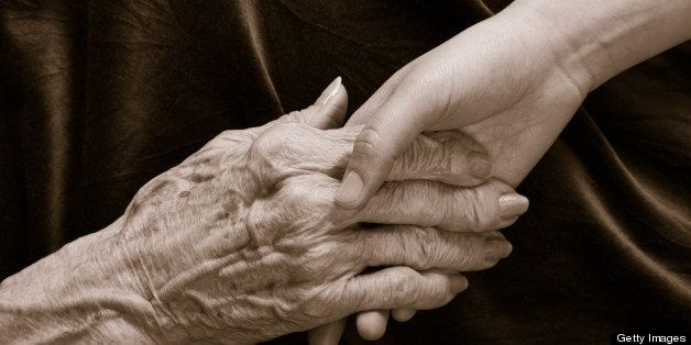 young hand holding old hand with arthritis, reaching and holding on dark cloth background