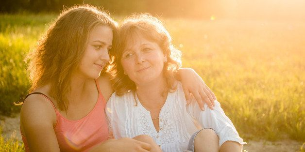 Happy mother sitting on grass in nature with her teenage daughter, flare from setting sun in photo