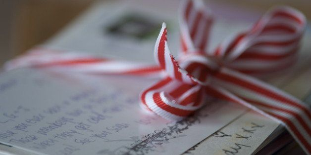 Post cards and letters written with love and tied with red and white striped ribbon.