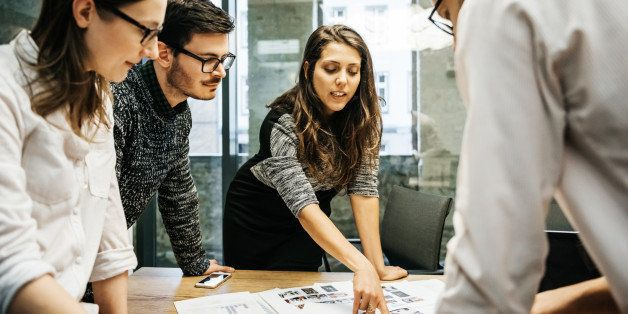A team of young people in a modern office is discussing their project. The group consists of two men and two women, one of th