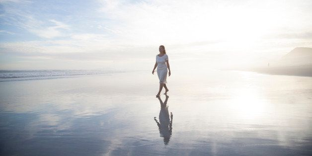 Woman walking alone on a misty beach