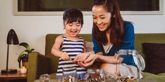 Lovely little girl putting coins into different glass jars on the coffee table joyfully under her pretty young mom's guidance