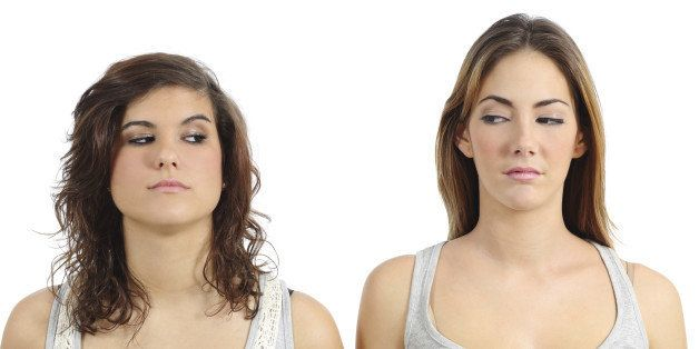 Two girls looking each other angry isolated on a white background