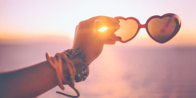 Cropped shot of a woman's hand holding a pair of heart-shaped sunglasses at sunset on a beach