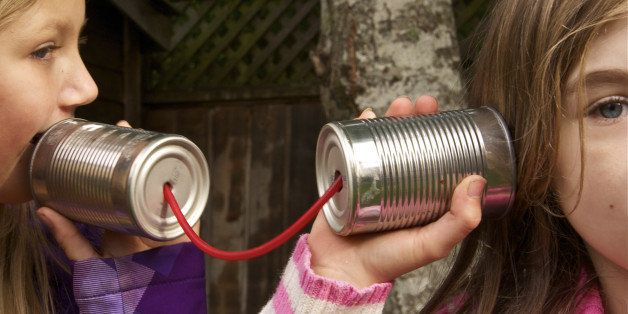 Two girls talking using tin cans connected by red string.