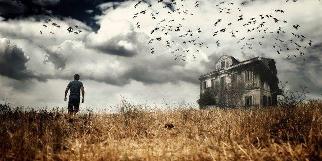 Man walking in a field towards a haunted house