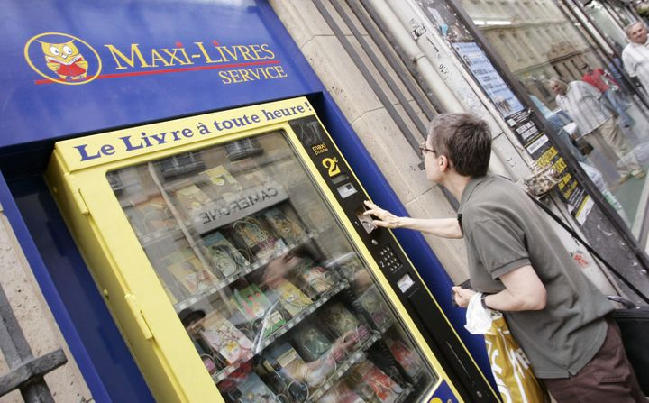 Paris, FRANCE:  A young woman buys a book from a street vending machine 19 August 2005 in Paris. The company announced the in