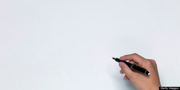 Man writing on white sheet of paper, close-up of hand