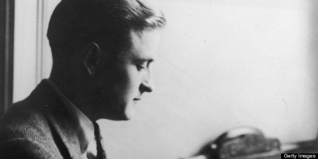 Profile view of American author F(rancis) Scott (Key) Fitzgerald (1896 - 1940) reading a book while sitting at a desk.   (Pho