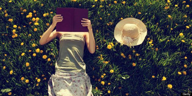 Girl lying in grass, reading a book