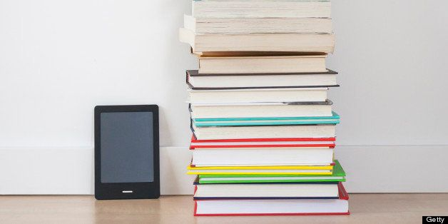 E-reader digital tablet sitting next to a stack of traditional hardcover books on the floor.